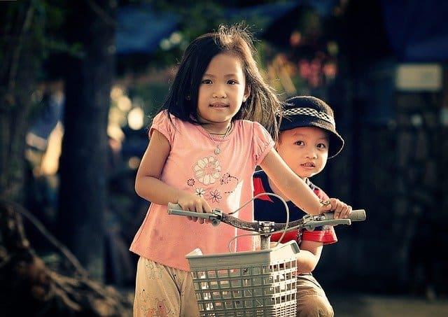 A little girl holding a bike