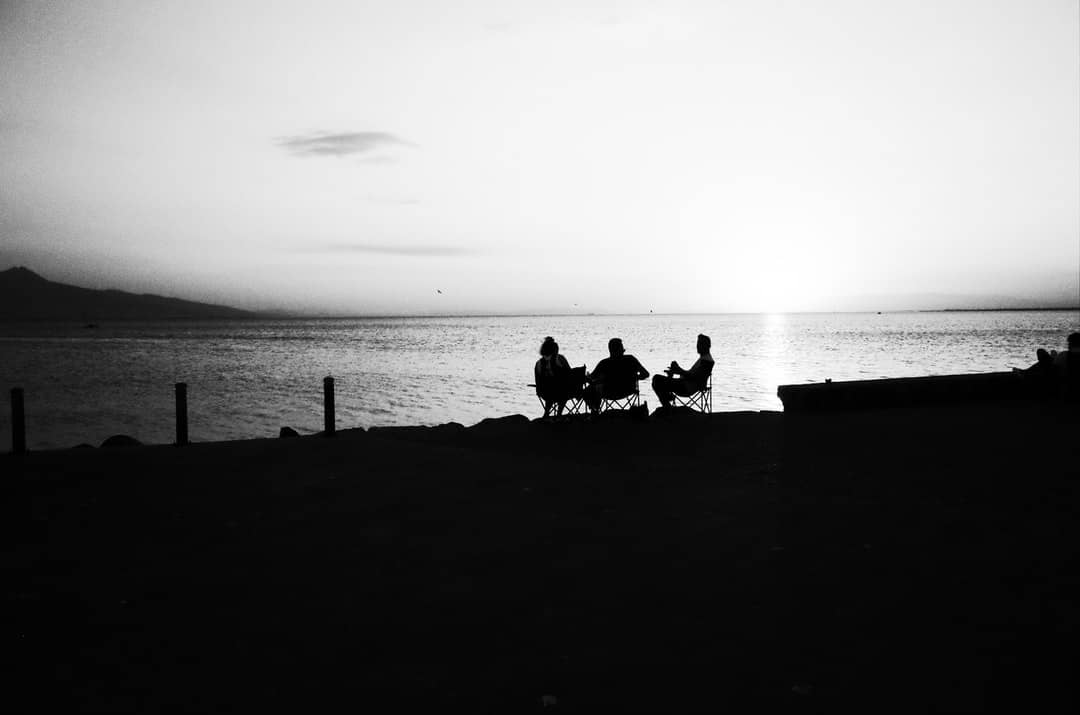 A group of people sitting at a beach near a body of water