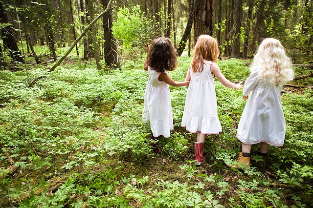 A little girl standing next to a forest