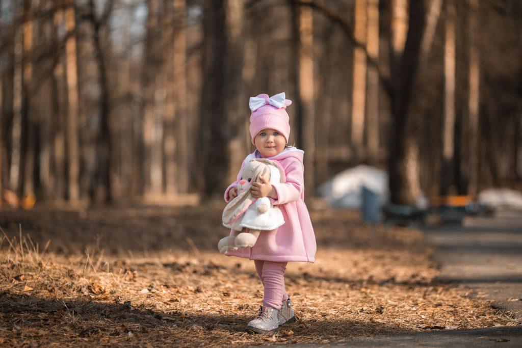A little girl walking down a dirt road